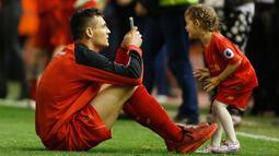 Bek Liverpool Dejan Lovren mengambil gambar putrinya saat salam penghormatan usai bertanding melawan Chelsea pada pertandingan Liga Inggris di Anfield, Liverpool, 12 Mei 2016. (Reuters / Carl Recine)