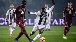 Gelandang Torino, Nicolas Nkoulou, berebut bola dengan gelandang Juventus, Blaise Matuidi, pada laga Serie A di Stadion Olympic, Turin, Sabtu (15/12). Torino kalah o-1 dari Juventus. (AFP/Marco Bertorello)