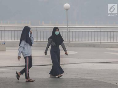 Dua wanita mengenakan masker saat mengunjungi alun-alun Kabupaten Siak, Riau, Kamis (12/9/2019). Asap pekat kebakaran lahan gambut tersebut selain mengganggu kesehatan serta mencemari udara sehingga kualitasnya turun ke status tidak sehat. (Liputan6.com/Faizal Fanani)