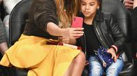 Penyanyi Beyonce dan putrinya Blue Ivy Carter berselfie saat menonton pertandingan NBA All-Star Game 2018 di Staples Center di Los Angeles, California, AS (18/2). (Allen Berezovsky/Getty Images/AFP)