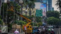 Sebuah mobil crane digunakan untuk membantu petugas memperbaiki lampu jalan di Kawasan KH Wahid Hasyim, Jakarta, Selasa (27/9). Perawatan rutin dilakukan untuk memastikan penerangan untuk jalan dan patung tetap berfungsi. (Liputan6.com/Faizal Fanani)