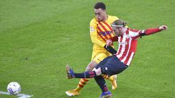 Striker Athletic Bilbao, Iker Muniain (kanan) melepaskan tendangan dibawah tekanan bek Barcelona, Sergino Dest dalam laga lanjutan Liga Spanyol 2020/21 di San Mames Stadium, Bilbao, Rabu (6/1/2021). Athletic Bilbao kalah 2-3 dari Barcelona. (AFP/Ander Gillenea)