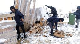 Para imigran mengumpulkan kayu bakar ke dalam tempat sampah di Kamp Lipa, luar Bihac, Bosnia, Jumat (8/1/2021). Cuaca bersalju dan musim dingin telah membawa lebih banyak penderitaan bagi ratusan imigran yang terjebak selama berhari-hari di kamp tersebut. (AP Photo/Kemal Softic)