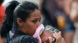Kerabat dari narapidana menangis di pos pemeriksaan menyusul kerusuhan yang terjadi di dalam penjara kota Amazon, Brasil, Senin (2/1). Beberapa korban yang berasal dari anggota geng narkotik Brasil tewas dengan tubuh terpenggal. (REUTERS/Michael Dantas)
