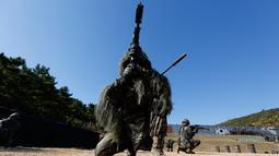 Seorang marinir beraksi selama latihan reguler di Pulau Yeonpyeong, Korea Selatan (1/11). Zona larangan terbang dan larangan latihan militer di dekat perbatasan yang dijaga ketat antara Korut dan Korsel mulai berlaku hari ini. (AP Photo/Jeon Heon-kyun)
