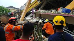 Tim penyelamat mencari korban yang terperangkap dalam sebuah bangunan runtuh di Mamuju, Sulawesi Barat, Indonesia, Jumat (15/1/2021). BMKG menyebut pusat gempa berada di darat, 6 kilometer timur laut Majene pada kedalaman 10 kilometer. (HANDOUT/NATIONAL SEARCH AND RESCUE AGENCY/AFP)