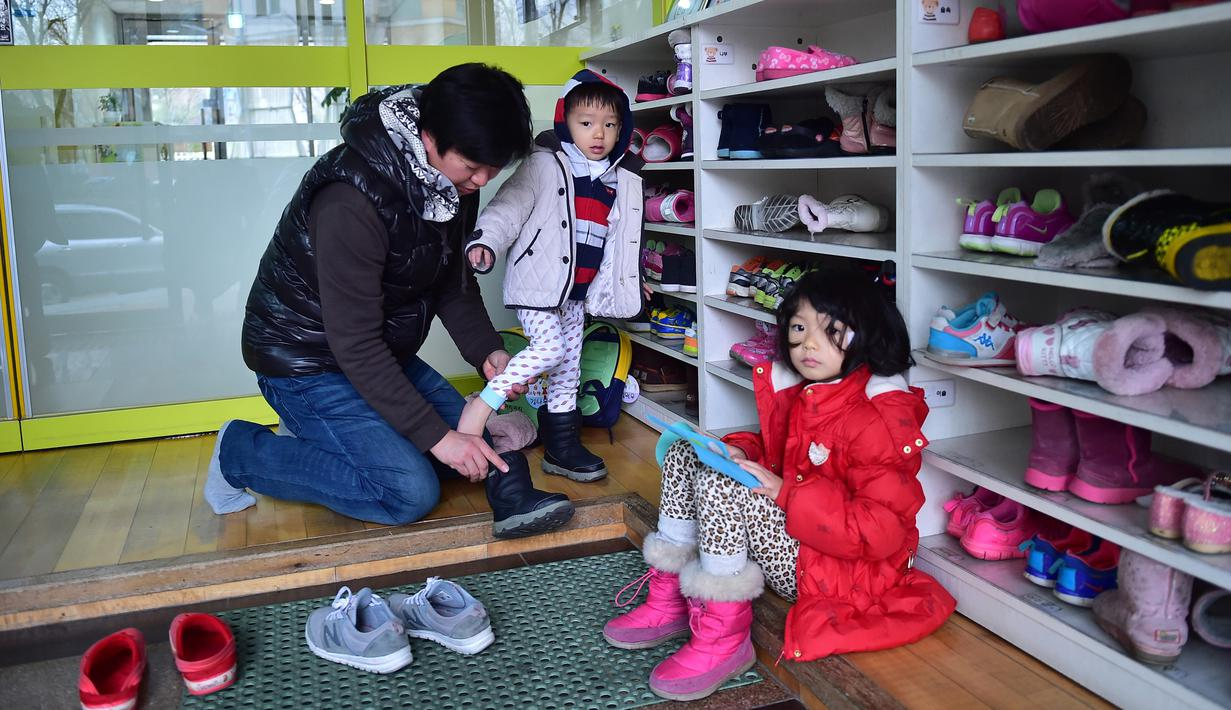 Kim Jin-Sung memakaikan sepatu anaknya Won-Woo di perawatan anak di Seoul. Kim adalah salah satu dari meningkatnya jumlah ayah di Korea Selatan memilih istirahat dari karirnya untuk membantu membesarkan anak-anaknya. (AFP PHOTO/JU)