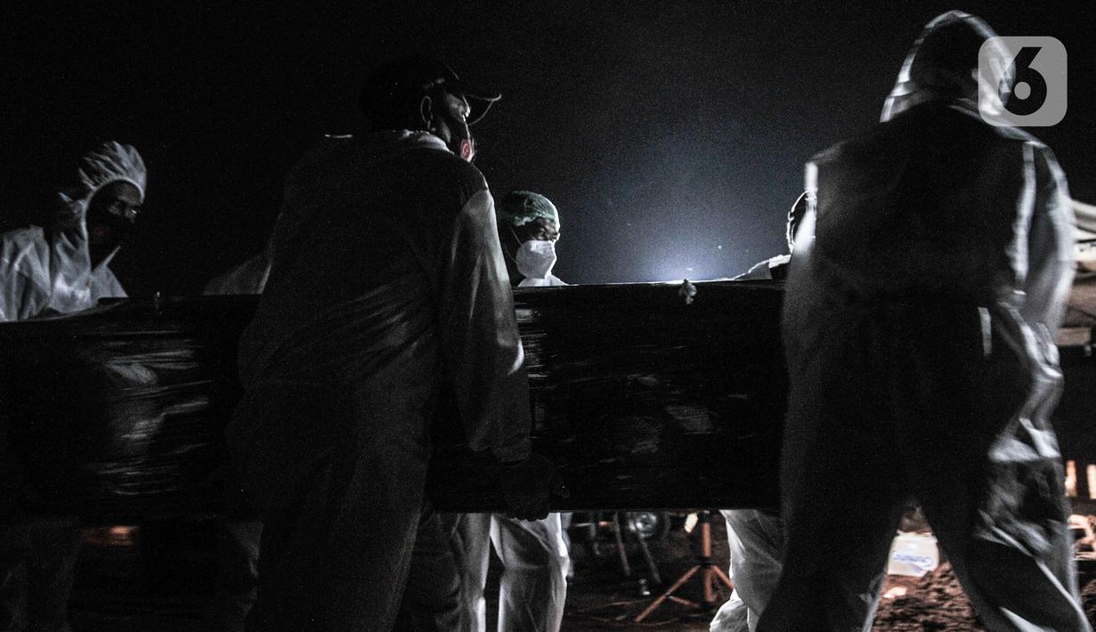 Petugas mengenakan alat pelindung diri (APD) dan baju hazmat saat proses pemakaman pasien Covid-19 di TPU Pondok Ranggon, Jakarta, Kamis (24/9/2020). Jumlah kumulatif kasus Covid-19 di Indonesia mencapai 262.022 orang per Kamis (24/9) dengan 10.105 jiwa meninggal dunia. (merdeka.com/Iqbal Nugroho)