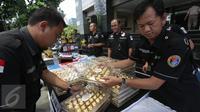 Dit Narkoba Polda Metro Jaya menata barang bukti hasil Operasi Bersinar Jaya 2016, Jakarta, Rabu (13/4). Petugas mengungkap peredaran narkoba internasional dengan mengamankan 36,43 kg shabu kristal yang dikemas kotak cokelat. (Liputan6.com/Gempur M Surya)