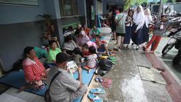 Warga yang rumahnya terendam banjir mengungsi di Gedung SMP Negeri 26, Jalan Kebon Pala, Kampung Melayu, Jatinegara, Jakarta Timur, Selasa (6/2). Sekolah masih tetap masuk, tetapi hanya diabsen karena tidak adanya listrik. (Liputan6.com/Arya Manggala)
