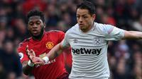 Striker West Ham United, Javier Hernandez berusaha menggiring bola dari kejaran gelandang Manchester United, Fred selama pertandingan lanjutan Liga Inggris di Old Trafford (13/4). MU menang tipis atas West Ham 2-1. (AFP Photo/Paul Ellis)