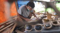 Perajin membuat kacamata berbahan baku kayu di Gang  Madrasah, Pamulang, Tangerang Selatan, Senin (21/1). Dalam sehari, pengrajin mampu menyelesaikan dua buah kacamata yang dijual antara Rp 200 ribu hingga Rp 500 ribu per buah. (Merdeka.com/Arie Basuki)