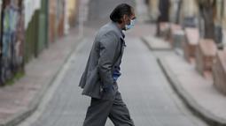 Pejalan kaki yang mengenakan masker menyeberang jalan di tengah lockdown yang diberlakukan kembali di Bogota, Kolombia, Sabtu (10/4/2021). Walikota Bogota Claudia Lopez memerintahkan lockdown hingga 13 April saat ibu kota mengalami peningkatan tajam infeksi COVID- 19. (AP Photo/Fernando Vergara)