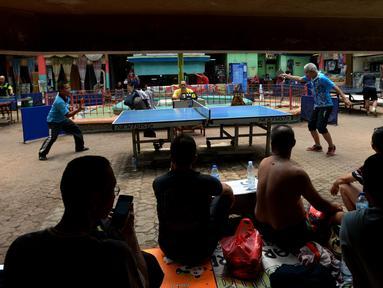Petenis melakukan servis ke arah lawannya saat kejuaraan Bintikers Cup Tenis Meja di Pasar Grogol, Jakarta, Sabtu (14/12/2019). Turnamen Bintikers Cup Tenis Meja diikuti 125 orang yang merupakan perwakilan pedagang pasar se-Jabodetak dan luar Jakarta seperti Surabaya. (merdeka.com/Imam Buhori)
