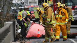 Penyidik melihat mayat korban akibat tabrakan antara dua truk besar di utara pusat kota Los Angeles (25/4). Kecelakaan ini menewaskan satu orang dan melukai sejumlah orang lainnya. (AP Photo/Reed Saxon)