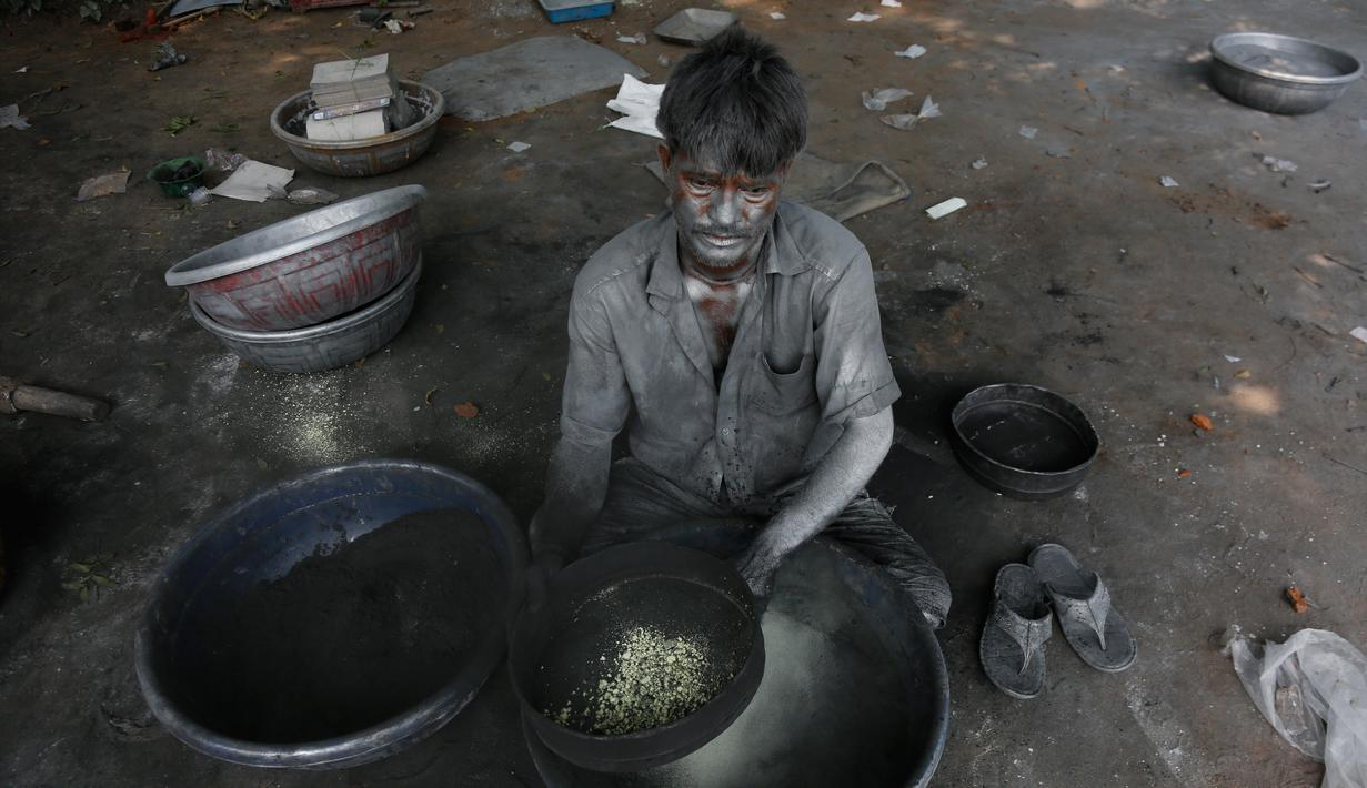 Seorang pria India meracik bubuk mesiu untuk membuat petasan yang digunakan dalam festival Diwali di Ahmadabad, India (27/9). Menjelang perayaan Diwali, sejumlah produsen petasan di India dibanjiri pesanan. (AP Photo/Ajit Solanki)