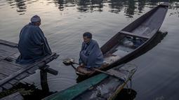 Orang-orang Kashmir mengobrol di pagi hari di dermaga di Danau Dal di Srinagar, Kashmir yang dikendalikan India (18/10/2020). (AP Photo/Dar Yasin)