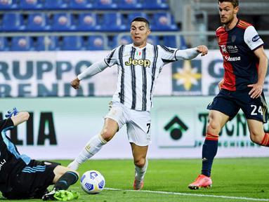 Striker Juventus, Cristiano Ronaldo, berusaha melewati kiper Cagliari, Alessio Cragno, pada laga Liga Italia di Sardegna Arena, Minggu (14/3/2021). Juventus menang dengan skor 3-1. (AFP/Albert0 Pizzoli)