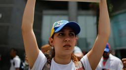 """Seorang dokter muda membawa poster bertuliskan """"You are killing us,"""" saat unjuk rasa menuntut Presiden Venezuela Nicolas Maduro di Caracas, Venezuela, (22/5). Sedikitnya 46 orang telah meninggal dunia. (AP Photo/Ariana Cubillos)"""