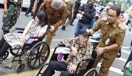 Gubernur DKI Jakarta Anies Baswedan mendorong penyandang disabilitas berkursi roda saat meresmikan pelican crossing di Halte Transjakarta Bank Indonesia (BI), Jakarta, Selasa (4/9). (Liputan6.com/Immanuel Antonius)