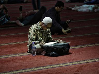 Jemaah membaca kitab suci Alquran usai salat di Masjid Istiqlal, Jakarta, Selasa (7/5/2019). Umat muslim meningkatkan ibadah pada bulan suci Ramadan dengan membaca Alquran (tadarus), salat berjemaah, berdoa, dan zikir di masjid. (Liputan6.com/Faizal Fanani)