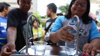 Warga mengambil air minum gratis saat run for water di CFD, Jakarta, Minggu (25/3). Run For Water kolaborasi PAM Jaya, Palyja, dan Aetra mengkampanyekan Hari Air Dunia 2018 mengajak masyarakat ayo peduli air Jakarta. (Liputan6.com/Angga Yuniar)