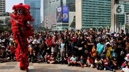 Warga menyaksikan pertunjukkan barongsai saat ajang car free day (CFD) di kawasan Bundaran HI Jakarta, Minggu (26/1/2020). Barongsai tersebut sengaja dihadirkan dalam rangka perayaan Imlek 2020 untuk menghibur para warga yang tengah mengikuti CFD. (Liputan6.com/Johan Tallo)