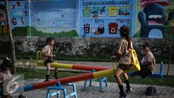 Anak-anak bermain ayunan di RPTRA di Jalan Pluit Mas Utara, Kelurahan Pejagalan, Kecamatan Penjaringan, Jakarta (6/4). Salah satu fungsi RPTRA adalah agar masyarakat bisa saling mengenal dan menjadi tempat bermain anak. (Liputan6.com/Faizal Fanani)