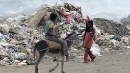 Seorang anak laki-laki menaiki kuda saat mengumpulkan sampah untuk didaur ulang di tempat pembuangan sampah di kota Houdieda, Yaman, Rabu (20/1). (REUTERS/Abduljabbar Zeyad)