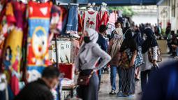 Sejumlah calon pembeli melihat-lihat pakaian yang dijual di Jembatan Penyeberangan Multiguna atau Skybridge Tanah Abang, Jakarta, Jumat (19/6/2020). Kendati pusat perbelanjaan telah dibuka sejak 15 Juli 2020, aktivitas jual beli di Skybridge Tanah Abang terpantau sepi. (Liputan6.com/Faizal Fanani)