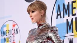 Penyanyi Taylor Swift menghadiri ajang American Music Awards 2018 di Los Angeles, Selasa (9/10). Mengenakan mini dress silver dari Balmain, Taylor langsung menjadi pusat perhatian begitu melangkah di red carpet. (Kevork Djansezian/Getty Images/AFP)