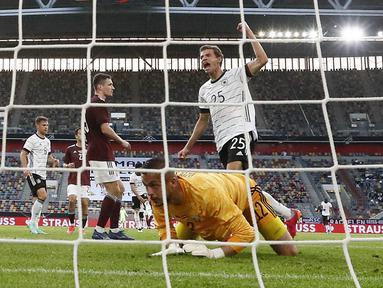 Penyerang timnas Jerman, Thomas Mueller berselebrasi setelah mencetak gol melewati kiper Latvia, Roberts Ozols dalam laga uji coba jelang EURO 2020 di Merkur Spiel Arena, Selasa (8/6/2021) dini hari WIB. Timnas Jerman memenangkan pertandingan dengan skor 7-1. (AP Photo/Martin Meissner)