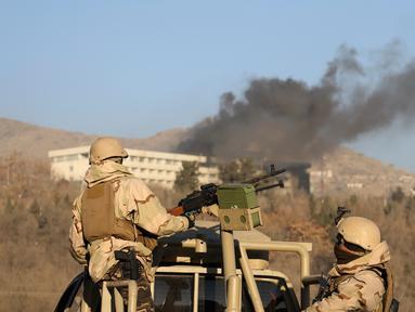 Pasukan keamanan Afghanistan berjaga saat asap keluar dari Hotel Intercontinental setelah terjadi serangan di Kabul, Afghanistan, Minggu (21/1). Orang-orang bersenjata menyerbu hotel mewah tersebut pada Sabtu, 20 Januari 2018 malam. (AP Photo/Rahmat Gul)