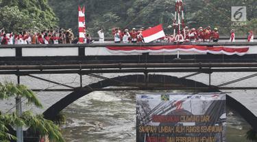 Bendera Merah Putih dikibarkan pada upacara peringatan HUT Kemerdekaan RI di Jembatan Panus, Depok, Kamis (17/8). Komunitas Ciliwung Depok melakukan pengibaran bendera di Jembatan Panus yang melintang di atas Sungai Ciliwung (Liputan6.com/Herman Zakharia)