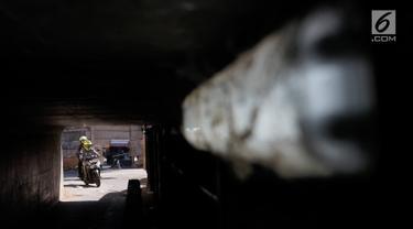 Pengendara motor melintasi terowongan di bawah Jalan Tol Jagorawi, kawasan Kampung Rambutan, Jakarta, Rabu (21/8/2019). Meskipun sempit dan gelap, namun terowongan itu menjadi akses alternatif pengguna jalan untuk menyeberangi Jalan Tol Jagorawi di kawasan tersebut. (Liputan6.com/Immanuel Antonius)