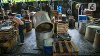 Pekerja merapikan tatakan di pabrik tahu tempe yang berhenti operasi di kawasan Duren Tiga, Jakarta, Sabtu (2/12/2021). Puskopti mengimbau kepada seluruh anggota untuk menaikkan harga jual tahu dan tempe minimal 20 persen dari harga awal untuk mengantisipasi kerugian. (Liputan6.com/Faizal Fanani)