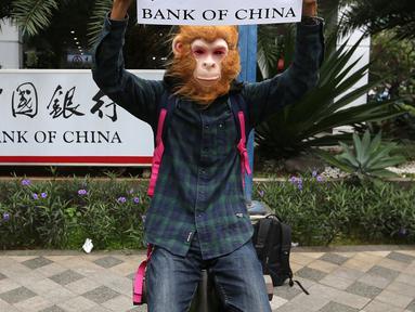 Aktivis WALHI memakai topeng orangutan saat menggelar aksi di depan Gedung Bank of China, Jakarta, Jumat (1/3). Aksi ini digelar jelang putusan PTUN Medan terkait gugatan WALHI terhadap izin lingkungan PLTA Batang Toru. (Liputan6.com/Fery Pradolo)