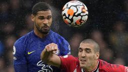 Gelandang Chelsea, Ruben Loftus-Cheek berduel udara dengan gelandang Southampton, Oriol Romeu dalam laga yang diguyur hujan di Stamford Bridge. (AP/Kirsty Wigglesworth)