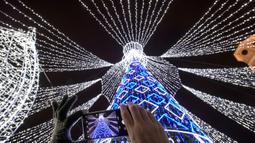 Seorang perempuan dengan smartphone memotret pohon Natal raksasa yang menerangi Alun-Alun Katedral di Vilnius, Lithuania, Minggu (1/12/2019). Secara tradisi, pohon Natal Vilnius biasanya berupa rangka logam yang ditutupi dengan dekorasi dan cabang-cabang pohon dari hutan. (AP/Mindaugas Kulbis)