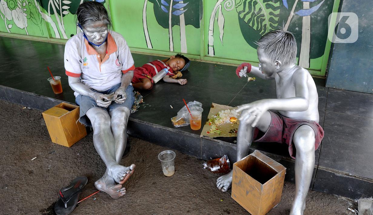 "Seorang ibu menghitung uang hasil mengamennya sebagai ""Manusia Silver "" bersama sang anak di salah satu sudut toko di kawasan perempatan Gaplek, Pamulang, Tangerang Selatan, Sabtu (16/1/2021). Ibu tersebut mendapat penghasilan sekitar 50 ribu per hari sebagai Manusia Silver (merdeka.com/Arie Basuki)"