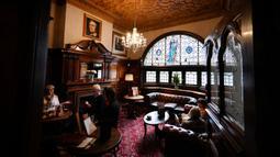 Orang-orang minum di pub Philharmonic Dining Rooms di Liverpool, Inggris pada 11 Februari 2020. Tempat yang berada di seberang arena konser Liverpool Philharmonic Hall ini terkenal karena tembok batunya yang mewah dan interiornya yang megah. (Paul ELLIS / AFP)