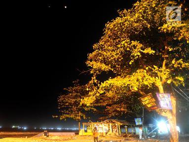 Warga menyaksikan pemandangan planet Mars berdampingan dengan gerhana bulan total terlihat di Karang Hawu, Pelabuhan Ratu, Sukabumi, Sabtu (28/7) dini hari. Fenomena alam ini menjadi gerhana Bulan paling lama Abad 21.  (Merdeka.com/Arie Basuki)