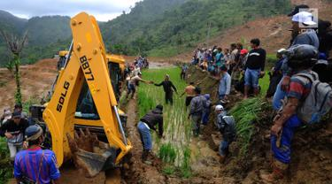 Warga memandu alat berat melalui jalan kecil menuju lokasi longsor di Dusun Cimapag, Sirnaresmi, Cisolok, Sukabumi, Jawa Barat, Selasa (1/1). Alat berat dikerahkan untuk mencari korban yang hilang. (Merdeka.com/Arie Basuki)