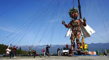 Pekerja mengatur boneka raksasa MOCCO saat sesi latihan khusus di Takamori, Prefektur Nagano, Jepang, Jumat (23/4/2021). Penyelenggara Olimpiade Tokyo menciptakan boneka setinggi sekitar 10 meter untuk melambangkan semangat masyarakat yang terdampak gempa dan tsunami 2011 lalu. (AP Photo/Koji Ueda)
