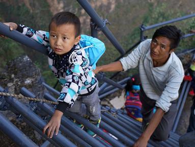 Sejumlah anak didampingi orang tua memanjat tangga baru menuju rumah yang berada di ketinggian 800 meter di Desa Atuleer, Tiongkok, Rabu (19/11). Pemerintah Tiongkok akhirnya membangun tangga untuk warga yang tinggal di desa tersebut. (REUTERS)