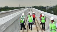 Menteri Perhubungan Budi Karya Sumadi mengecek pemasangan lintasan kereta dari atas lokasi LRT rute Cawang-Cibubur di tol Jagorawi Km 13, Jakarta, Minggu (8/1). Proyek LRT tahap 1 Cibubur-Cawang baru selesai 15 persen. (Liputan6.com/Helmi Afandi)
