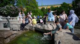 Orang-orang menikmati musim semi yang panas dekat air mancur di luar Kremlin, Moskow, Rusia, Selasa (18/5/2021). Suhu di Moskow telah mencapai 31 derajat Celcius. (Natalia KOLESNIKOVA/AFP)
