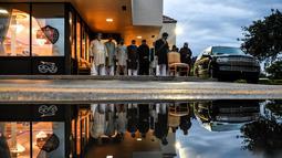 Refleksi pria Muslim terlihat dari genangan air saat mereka salat di trotoar di luar restoran selama bulan suci Ramadhan di Lauderhill, Florida, Jumat (30/4/2021). Selama puasa Ramadhan, umat Islam tidak makan, minum, atau aktivitas seksual dari fajar hingga matahari terbenam. (CHANDAN KHANNA/AFP)