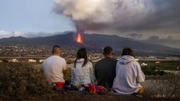 Warga menyaksikan lava mengalir dari gunung berapi yang meletus di Canary, Pulau La Palma, Spanyol, 26 Oktober 2021. Aliran lava baru telah muncul setelah runtuhnya sebagian kawah dan mengancam akan menelan daerah yang sebelumnya tidak terpengaruh. (AP Photo/Emilio Morenatti)