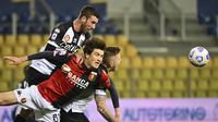 Striker Genoa, Eldor Shomurodov (depan) berebut bola dengan bek Parma, Mattia Bani (atas) dalam laga lanjutan Liga Italia 2020/2021 pekan ke-28 di Ennio Tardini Stadium, Parma, Jumat (19/3/2021). Genoa menang 2-1 atas Parma. (LaPresse via AP/Massimo Paolone)